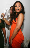 Ashanti shows a lot of cleavage in orange dress as she attends the Ashanti Listening Party at the W New York Downtown Hotel & Residences, in New York